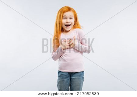 Feeling great. Positive delighted child keeping smile on her face and raising eyebrows while posing on camera poster
