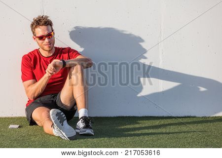 Smartwatch sport man checking progress on smart fitness watch post workout training. Athlete in sunglasses relaxing using online app on wearable device. Outdoor summer active lifestyle.