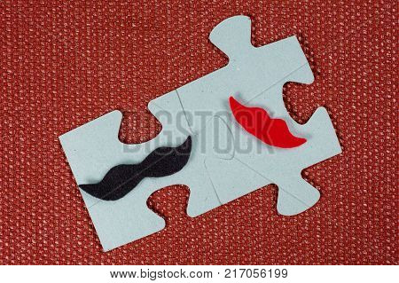 Close-up of 2 pieces of a puzzle. A symbolic man with a mustache and a woman with lips. The concept of psychological compatibility