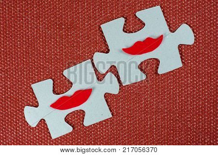 Close-up of two parts of a puzzle. Symbolic women with lips. The concept of psychological compatibility, friendship.
