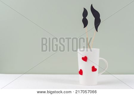 Valentine's day romantic background. Cup with hearts, couple - paper black mustache and paper black mustache