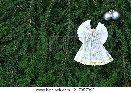 green Christmas background with paper ange fir branches and silver balls