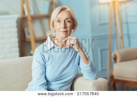 Smiling lady. Cute adorable senior woman looking kind and peaceful while sitting on a comfortable sofa with her fingers touching the chin and slightly smiling