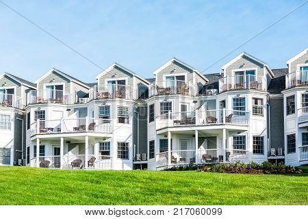 Wooden seaside hotel inn exterior with balconies green grass lawn nobody on sunny bright day