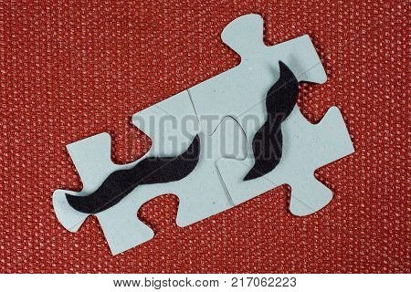 Close-up of two parts of a puzzle. Symbolic men with a mustache. The concept of psychological compatibility, friendship.
