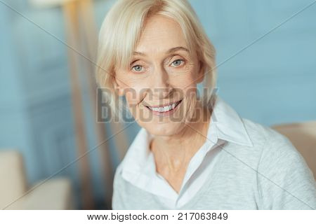 Baby boomer. Cute lovely aged woman having a good day and looking cheerful while standing and smiling happily