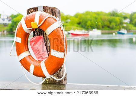 Empty marina harbor in small village of Rockport Maine during rain with boats and orange life buoy or lifebuoy