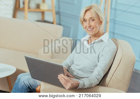 Very convenient. Smiling emotional progressive pensioner sitting in an armchair and feeling confident while holding a modern convenient laptop