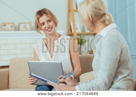 Experienced worker. Clever enthusiastic financial advisor holding a laptop and smiling cheerfully while looking at her calm aged client