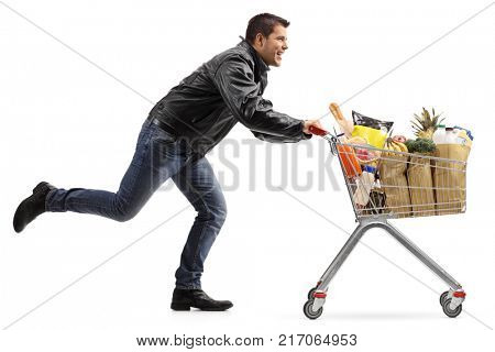 Full length profile shot of a biker running and pushing a shopping cart filled with groceries isolated on white background