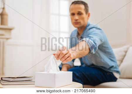 Emotion flow. Dismal reckless sad man sitting and stretching for tissue which placed on the table