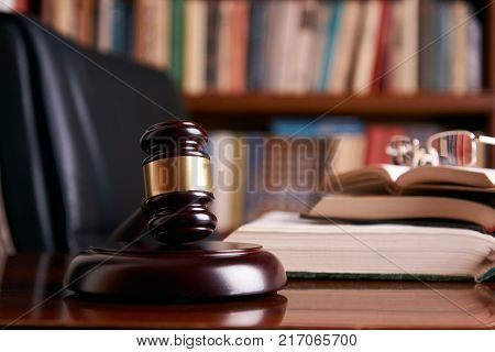 Judge gavel or law mallet and eyeglasses on a wooden desk, law books background. Education and legal law concept