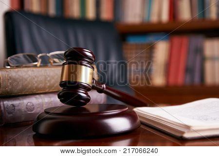 Judge's Gavel or mallet on wooden table with law books and eyeglasses, library background. Courtroom theme close-up. Education and legal law concept