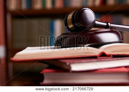 Law concept. Judges gavel with law books on wooden table in a courtroom or enforcement office, close-up