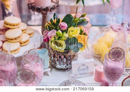 White wedding cake decorated by flowers standing on festive table with lots of snacks on side.