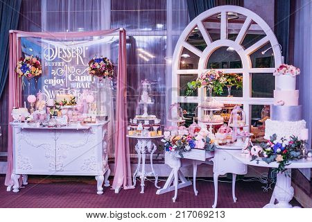 Delicious sweets and fruits on candy buffet. Lot of colorful desserts on table. Chocolate fountain. Party catering.