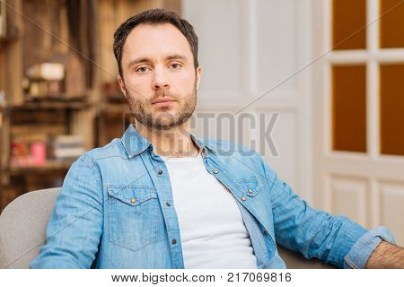 Disappointing truth.  Upset earnest young man sitting  staring at the camera while posing on the blurred background