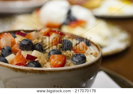 A bowl of yogurt parfait topped with strawberries, apples, blueberries and granola,