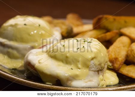 Eggs Benedict smothered in creamy hollandaise sauce, served with potato wedges