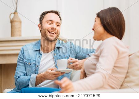 Sincere laugh. Positive nice optimistic man has fun with woman while sitting and enjoying coffee