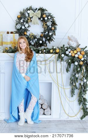 Pretty nine year old girl in pajama and covered with a blanket posing near the fireplace decorated for Christmas. Time for miracles.
