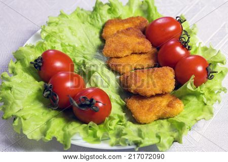 Close-up. Chicken nagets in breadcrumbs on green lettuce leaves with tomatoes in a white plate.