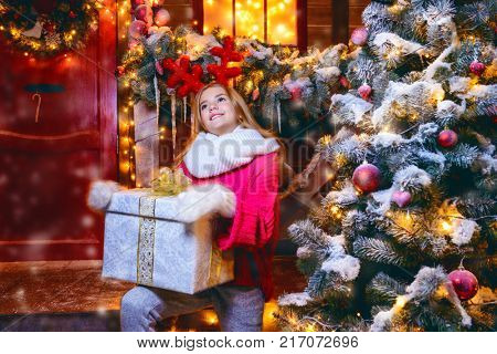 Pretty child girl is sitting on the porch of a house decorated for Christmas and holding a gift. Time for miracles.