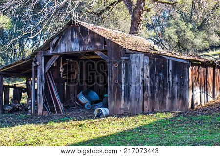 Old Weathered Wooden Shed With Debris On Tin Roof