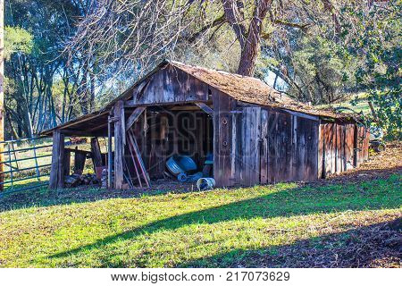Vintage Wooden Shed With Debris On Rusty Tin Roof