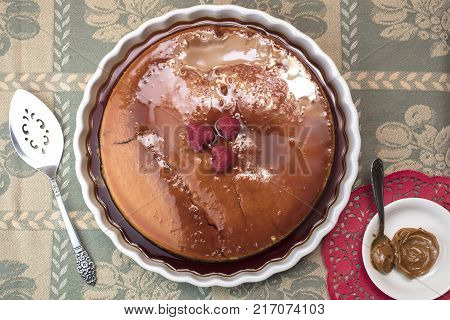 Creamy Flan dessert served with raspberries and dulce de leche served on a white plate