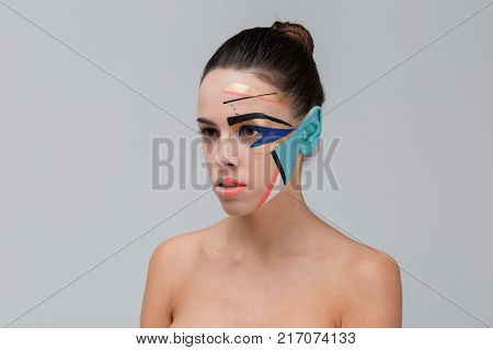 Close-up portrait of a brunette, in the studio, with bare shoulders, with bright geometric make-up, blue ear, make-up concept, serious girl looking away.