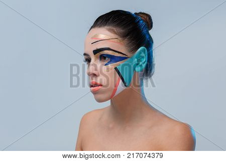 Close-up brunette in profile, in studio, with bare shoulders, with bright geometric make-up, blue ear, make-up concept, serious girl looking away.