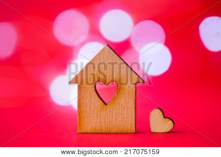 Wooden House With Hole In Form Of Heart With Little Heart On Pink Bokeh Background