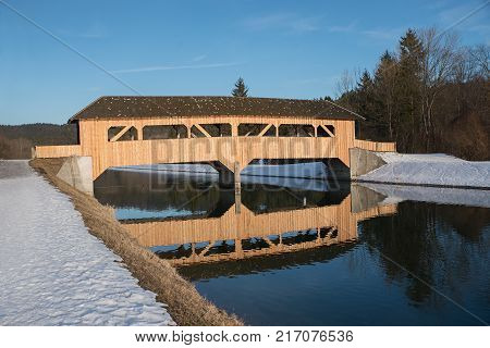wooden bridge over isar river, reflecting in the water, on a bright sunny winter day