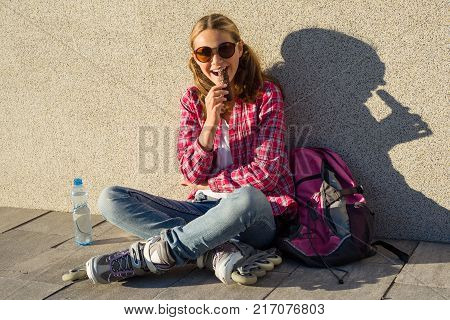 A young smiling cool girl, shod on roller skates, sits on the sidewalk, with a bottle of water, a backpack and eating chocolate bar. Sports, health and active leisure.