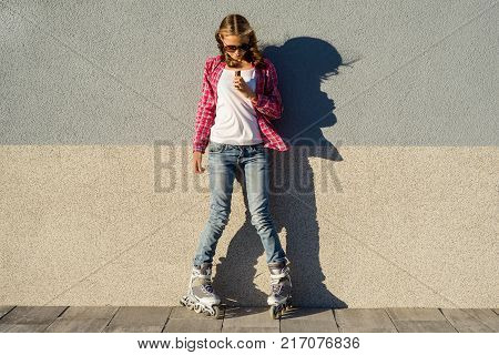 A young  cool girl, shod in rollerblades holding and eating chocolate bar. Energy and enjoyment