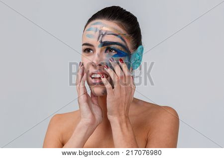Close-up of a brunette, in the studio, with bare shoulders, with smeared geometric make-up, blue ear, make-up concept, hands folded at the chin, looks away, smiles, parted mouth.