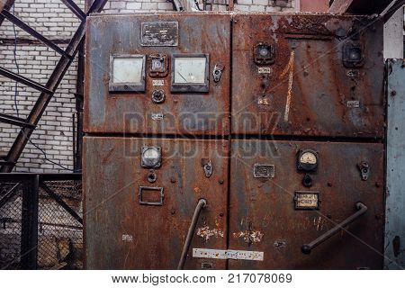 Old rusty electrical switchboard in abandoned factory.