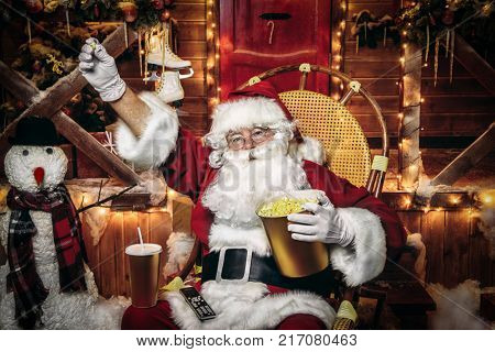 Santa Claus sitting on his armchair eating popcorn, drinking soda and watching a Christmas movie. Entertainment and cinema concept. Merry Christmas and Happy New Year.