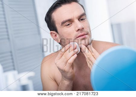 Tonic power. Appealing pensive young man using disc for applying tonic and wiping his face