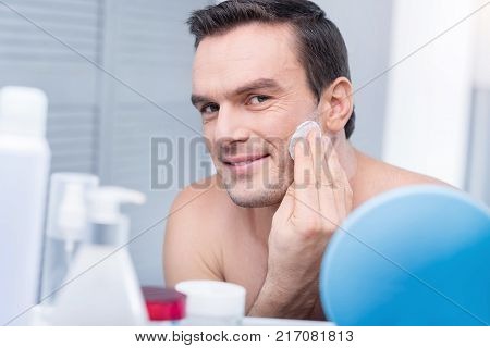 Fresh tonic. Irresistible magnetic gay man staring at the camera while cleaning his face and posing against light background