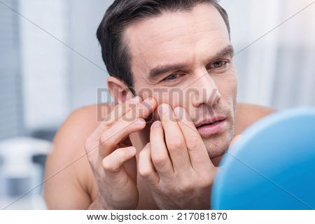 Annoying pimples. Cute earnest brunette man getting rid of pimples when placeng hands on the face  and  looking  at the mirror