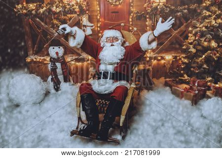 Santa Claus sitting on his armchair and watching a Christmas movie. Entertainment and cinema concept. santa claus and Happy New Year.