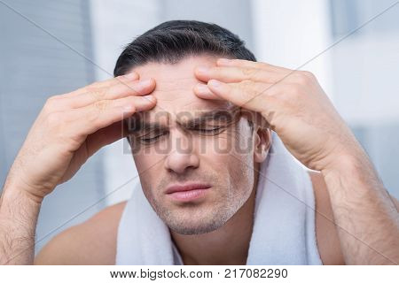 Massage relaxes.  Earnest anxious handsome man with closed his eyes touching his forehead while posing on the blurred background