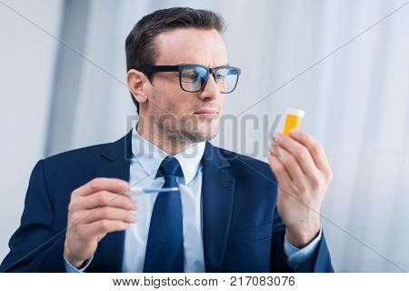 Interesting bottle. Thoughtful earnest confident man holding yellow bottle while examining it and wearing glasses