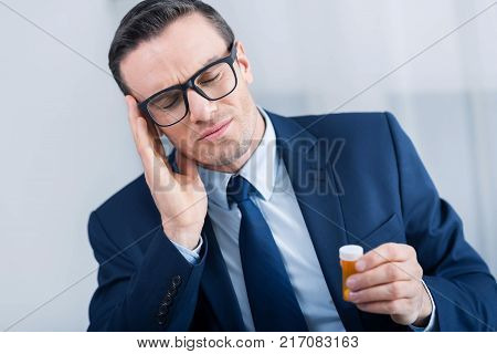 Terrible experience. Depressed exhausted young man touching his head with closed eyes while holding medication