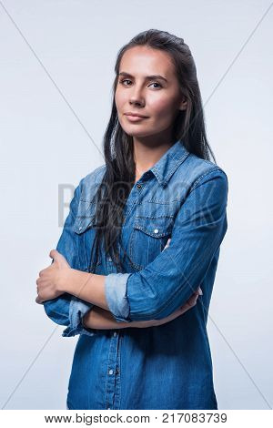 Bad behavior. Concentrated wistful young woman posing with crossed arms looking at the camera and reflecting