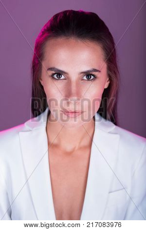Irresistible look. Prominent gorgeous pretty woman seducing you while posing against violet background and gazing at the camera