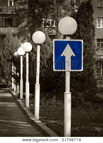 Blue arrow sign on a sepia photo of a line of lanterns