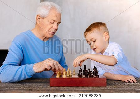 Intellectual game. Pleasant nice aged man sitting opposite his grandson and looking at the chess board while playing chess with him